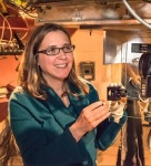"""<a href=""""https://www.ucsc.edu/"""">Alumna Shelley Wright, now an assistant professor of physics at UC San Diego (US), discusses the dichroic filter of the NIROSETI instrument, developed at the U Toronto Dunlap Institute for Astronomy and Astrophysics (CA) and brought to UCSD and installed at the UC Santa Cruz (US) Lick Observatory Nickel Telescope (Photo by Laurie Hatch).</a>"""